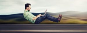 man working on laptop at high speed in an invisible car | streamline your EOS Level 10 Meetings