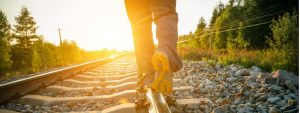 person walking on train tracks | EOS software to keep rocks on track