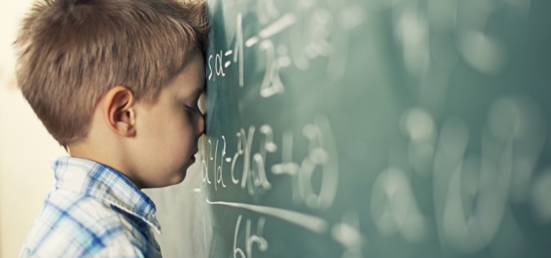 frustrated boy with head on chalkboard