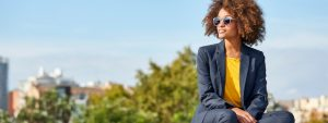 Young businesswoman sitting on retaining wall | close out your quarter