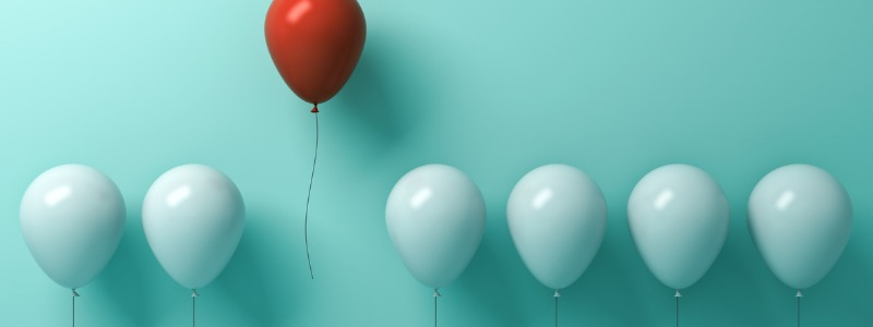one red balloon floating above many blue balloons   the outsiders book reveals great CEOs