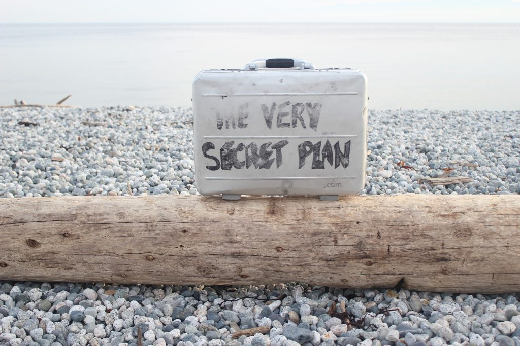 attache case on a beach with writing on it: the very secret plan