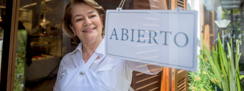 Latin American business woman holding an Open sign   EOS in Latin America