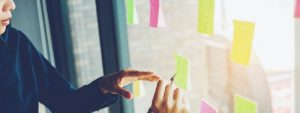 coworkers write on post-it notes that are posted on a window | building out your Accountability Chart