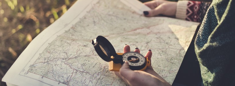 woman using a compass in the woods | should your company self-implement EOS?